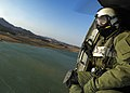 US Navy 060328-N-6074Y-093 Aviation Warfare Specialist 2nd Class Zack Webb, an air crewman assigned to Helicopter Anti-Submarine Squadron Two (HS-2) Golden Falcons, crouches in the door of an SH-60F helicopter.jpg