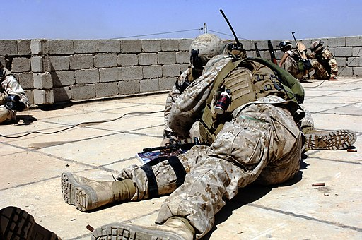 US Navy 060428-N-7497P-099 U.S. Marines take a low position and formulate a battle strategy to flush insurgents from their fighting positions during a rooftop gun battle in Ramadi, Iraq