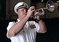 US Navy 080905-N-1161Z-077 Lt. Cmdr. Mark Grob, an auxiliaries officer aboard the aircraft carrier USS George Washington (CVN 73), plays taps on his trumpet during a burial at sea.jpg