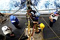 US Navy 100324-N-7948C-252 Aviation Ordnanceman Airman Raymond Thomas detaches the span line as Boatswain's Mate 2nd Class Bradley Gnage assists during an underway replenishment.jpg