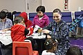 US Navy 110322-N-0640G-056 Aviation Maintenance Administration Airman Amanda Bowers plays with children while their parents process through customs.jpg