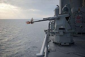 US Navy 120127-N-KS651-510 An MK38 MOD 2 25mm machine gun system aboard the amphibious dock landing ship USS Pearl Harbor (LSD 52) fires rounds dur.jpg