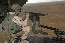 M240 machine gun mounted on V-22 loading ramp with a view of Iraq landscape with the aircraft in flight.