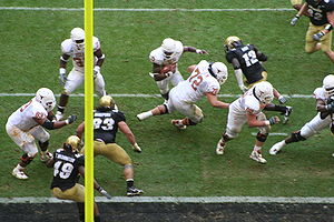Texas Longhorn quarterback Vince Young (center top of picture), now with the Tennessee Titans, rushing for a touchdown vs. Colorado in the 2005 Big 12 Conference college football championship game. A portion of the end zone is seen as the dark strip at the bottom. The vertical yellow bar is part of the goal post.