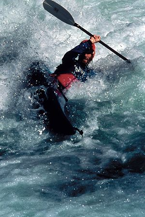 Whitewater - A solo kayak paddler performs a high brace in foamy water. One of the hazards of whitewater paddling is that highly aerated water decreases the effect of buoyancy.