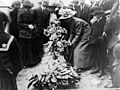 """Women, men, and children gather around a funeral wreath honoring """"Annie,"""" a victim of the Triangle fire. (5278899925).jpg"""