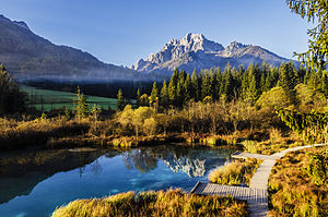 Zelenci - View towards the southeast: Lake Zelenci with the observation trail. In the background, the Martuljek Mountains.
