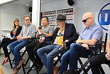 The panel seated in director's chairs