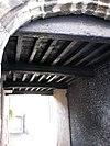foto van Gotische korfboog aan de zijde van de Beursstraat doorgang afsluitend bewerkte sleutelstukken. De boog ontspringt op gebeeldhouwde draagsteentjes (waarvan een verdwenen). Twee schamppalen