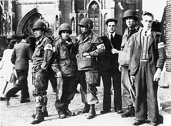 Members of the Dutch Eindhoven Resistance with troops of the US 101st Airborne Division in front of the Eindhoven cathedral during Operation Market Garden in September 1944.