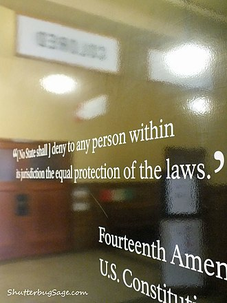 """Brown v. Board of Education National Historic Site - Quote from the 14th Amendment just inside the Monroe School entrance. The """"Colored"""" and """"White"""" signs from the segregationist era are reflected in the Amendment."""