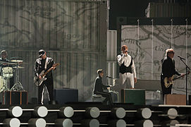Five men performing on a stage, with four of them playing instruments.