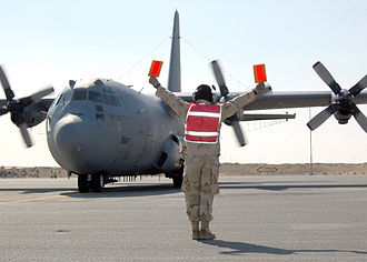 386th Air Expeditionary Wing - Staff Sgt. Jeffrey Weeks, 386th Expeditionary Aircraft Maintenance Squadron, marshals an EC-130H Compass Call on the flightline