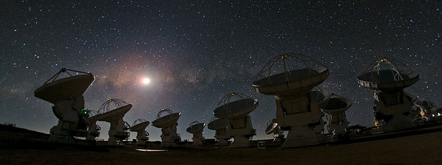 The ALMA radio telescopes under a starry sky