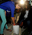 A child and a member of AmeriCorps Boys and Girls Club light one of the luminarias lining the sidewalk along U.S. Highway 90 during the Lights on After School celebration in Biloxi, Miss., Oct. 20, 2011 111026-F-BD983-001.jpg