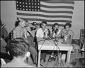 "A group of POWs being interviewed by the press at Freedom Village, Korea, proudly display their camp mascot ""Oscar"" a... - NARA - 542274.tif"