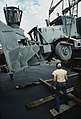 A longshoreman watches as an Oshkosh dump truck, equipped with a snow plow, is loaded aboard a barge by crane during Operation XOOL BARGE '88, a resupply mission by which goods and - DPLA - 8f6c87e583bab1c252e2ae39b47c68c3.jpeg