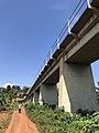 A man walks along a road parallel to the train bridge in Jinja town, Uganda.jpg