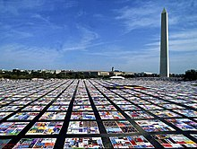 Squares of a quilt laid out in sections in a grid-like pattern, on a large, flat paved surface. The Washington Monument, a tall obelisk, can be seen in the background.