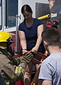 Airman 1st Class Colleen Erickson hands a hose to a Post 9463 Fire Explorer.jpg