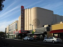 "A color photograph of a movie theater facade and street scene. The theater is designed in the Streamline Moderne style, with Moorish elements, and a blade which reads ""Alameda"" standing vertically above a marquee announcing films."