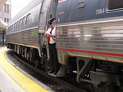 An Amtrak conductor standing in the doorway of an Amfleet cars with its trapdoor in the open position