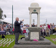 A balding man wearing a suit and playing a bugle, while standing in front of a crowd of other people and a stone monument.