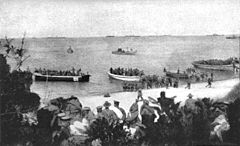 Boats carrying soldiers conduct a beach landing