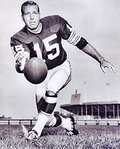 "Bart Starr in a Green Bay Packers football uniform poses while underhand tossing a football toward the camera. He is wearing number ""15""."