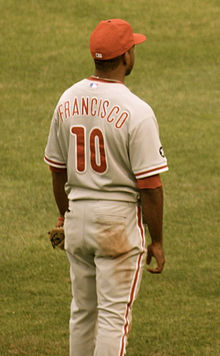"A view from the back of a dark-skinned young man in a gray baseball uniform and red baseball cap; the rear of his jersey reads ""Francisco"" in block red letters and ""10"" in larger red numbers"