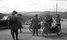 black and white photograph of a military car and two motorcycles with dismounted soldiers, some with a plume of feathers attached to their helmets