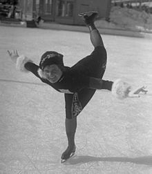 A woman wearing a dress and gloves is skating on an ice rink