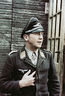 Color portrait of a man wearing a peaked cap, military uniform with an Iron Cross displayed at his neck.