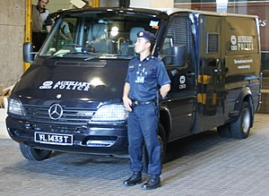 A CISCO Security auxiliary police officer stands guard beside an armoured truck while his colleagues deliver high-valued goods to and from commercial clients at Raffles Place, Singapore.