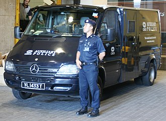 Singapore Police Force - A Certis CISCO auxiliary police officer stands guard beside an armoured truck at Change Alley, Singapore.