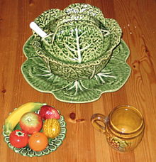top center: a cabbage-shaped tureen; bottom left: decorative plate with ceramic fruits and walnut; bottom right: barrel-shaped mug with grape motif
