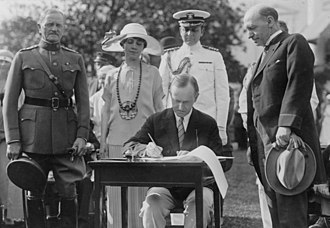 Calvin Coolidge - President Coolidge signing appropriation bills for the Veterans Bureau on the South Lawn during the garden party for wounded veterans, June 5, 1924. General John J. Pershing is at left. The man at right, looking on, appears to be Veterans Bureau Director Frank T. Hines.