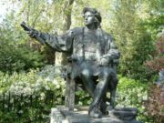 A bronze statue of Columbus sits among the flowers and trees of Belgrave Square, London.