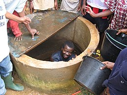 Man cleaning a well in Yaoundé, Cameroon