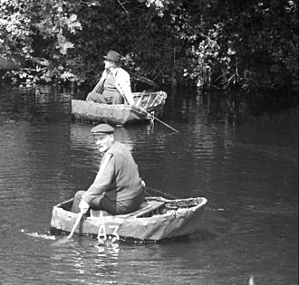 Coracle - The River Teifi, West Wales The two men are John Davies (forefront) and Will Davies of Cenarth;  the last two legitimate coracle fishermen in Cenarth. They are both using the single-arm method of propulsion; a means of gliding downstream in a controlled way. They carry their coracles and their fish home on their backs. (1972)