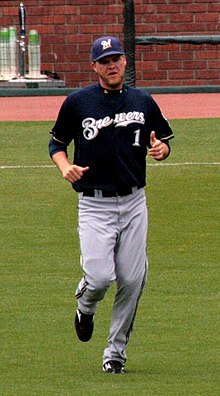 "A man wearing gray pants, a navy blue jersey with ""Brewers"" written in white, and a navy blue cap bearing a white ""M"" running on a baseball field"