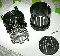 Una calculadora Curta parcialmente desmontada, mostrando los deslizadores de dígitos y el tambor de paso detrás de ellos.