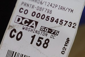 Bag tag - Example of IATA airport code printed on a baggage tag, showing DCA (Ronald Reagan Washington National Airport).