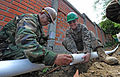 Defense.gov News Photo 110105-N-7589W-087 - U.S. Navy Petty Officer 1st Class Carlos Sanchez left assigned to Naval Mobile Construction Battalion 28 Detail Bravo applies concrete sealant.jpg