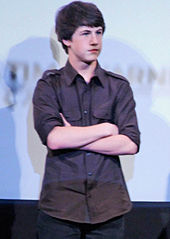 A teenage boy is standing up, with his arms crossed.
