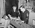 Electronics technicians working on equipment aboard USS Baltimore (CA-68) in the 1950s (NH 98242).jpg