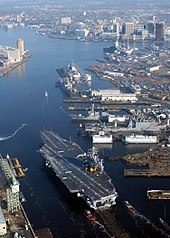 A large gray aircraft carrier sails down a river where the shore is lined with piers and large buildings.
