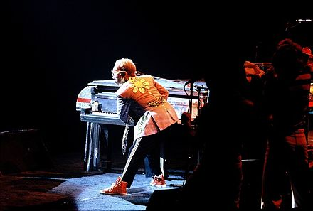 Elton John on the piano during a live performance in 1975 Elton John.jpg