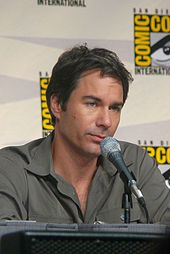 A caucasian male with dark hair wearing a grey shirt is facing to the right. A microphone is in front of him.