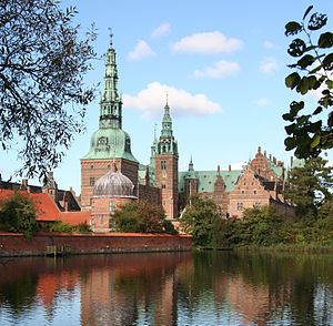 A palace, with several copper-covered spires, a dome, and tiered wings with dormers, is reflected in a large artificial lake in the foreground.